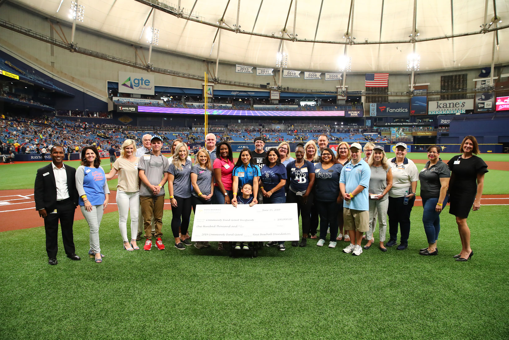Group photo with oversized check inside Tropicana Field.