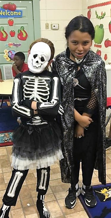Two students posing in halloween costumes.