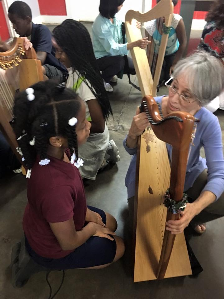Mentor teaching a student to play the harp.