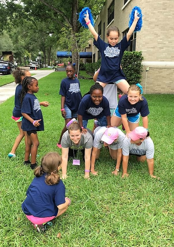 Students outside creating a human pyramid.